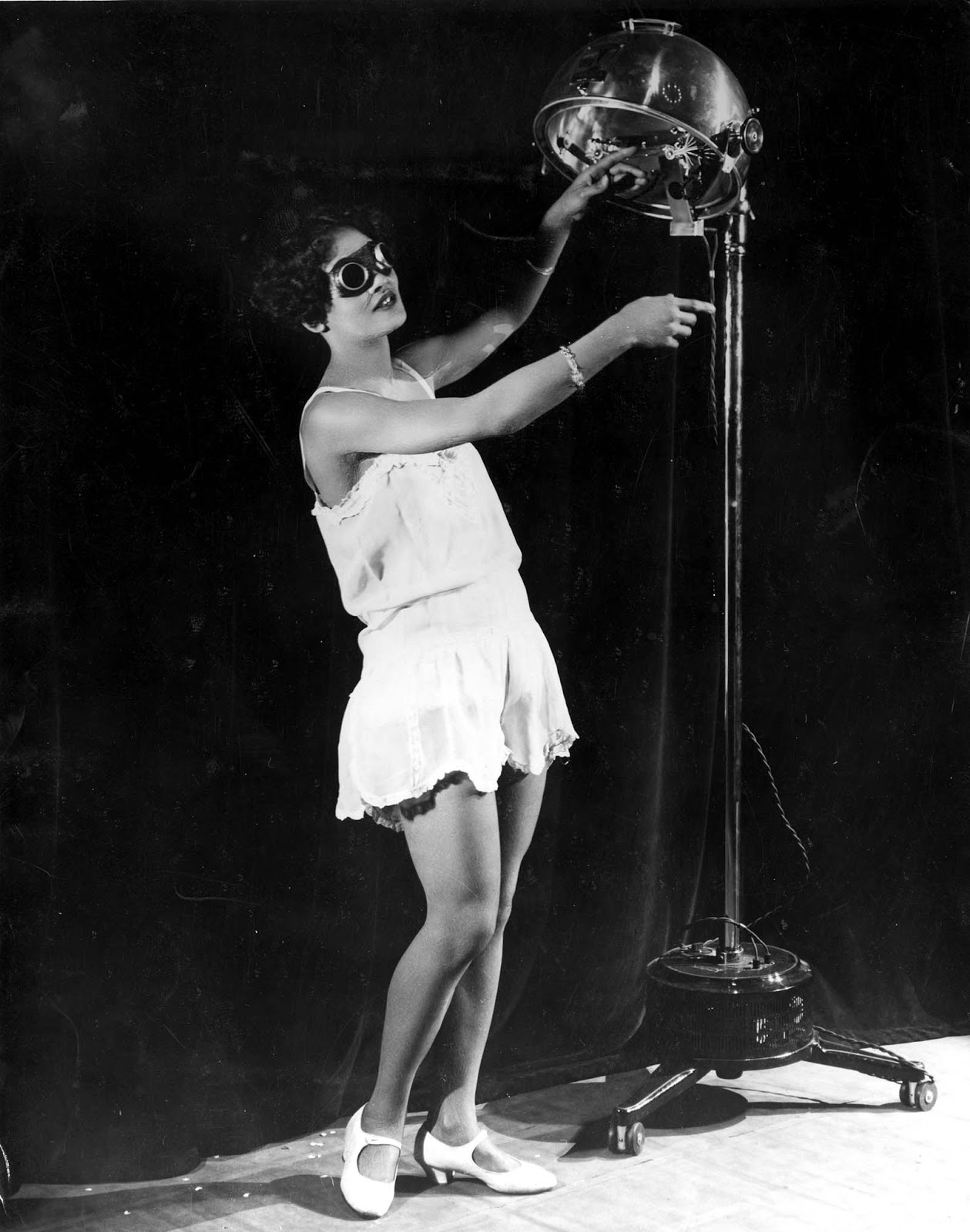 23 year old Alma Smith, the 'cleverest soubrette' of the cast of 'Blackbirds' at the London Pavilion, receiving her daily dose of ultra violet rays from a sun machine. 1929.