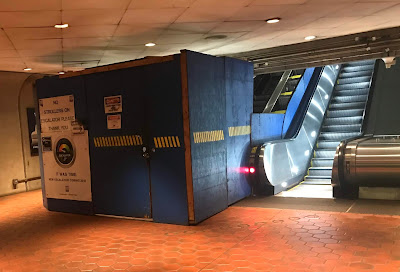 Photo of the mid-level landing showing a blocked off escalator under construction and an operational escalator