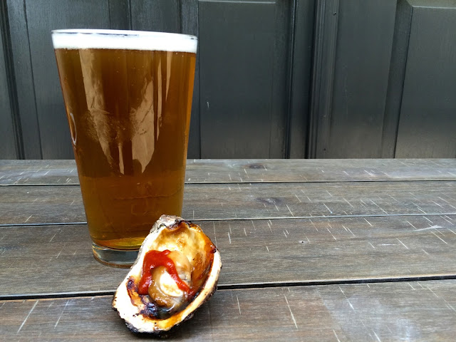 A pint of Tin Roof Brewing's Turnrow Harvest Ale and the Asian Style Chargrilled Oyster at Jolie Pearl Oyster Bar