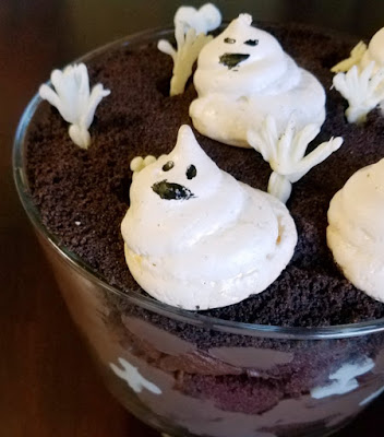 layers of chocolate in glass trifle bowl with white chocolate hands and meringue ghosts on top