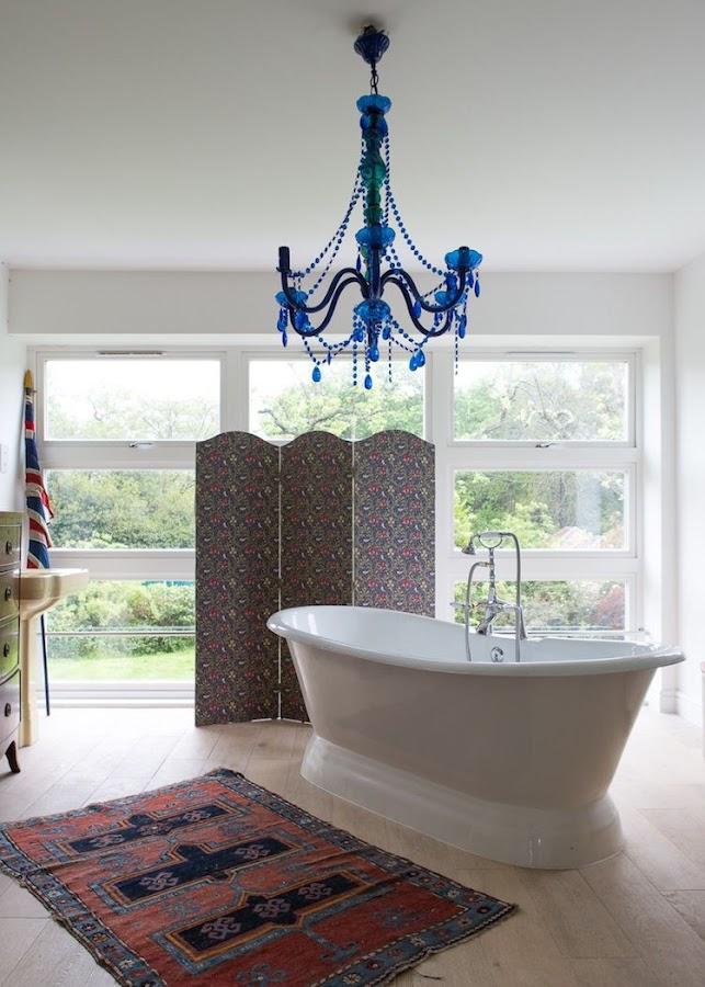 bañera exenta bajo lámpara de cristal azul