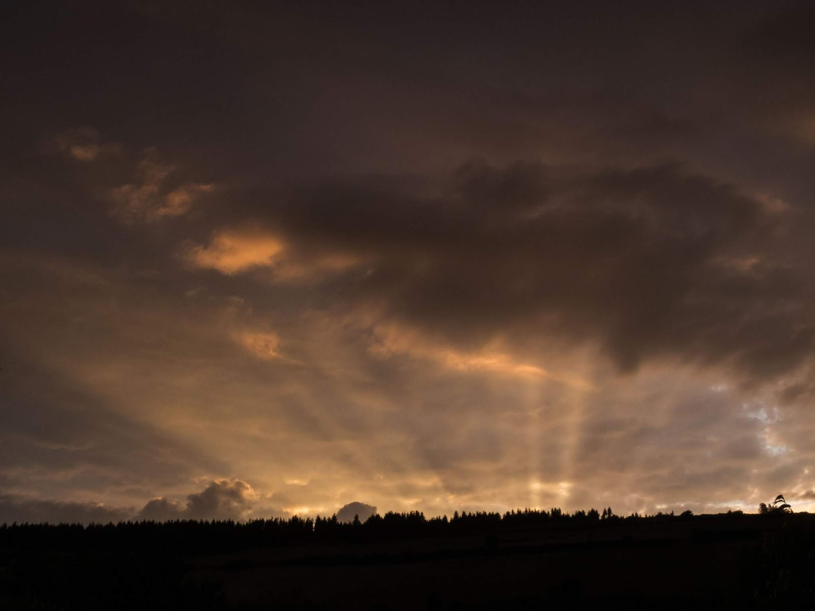Orange sunset rays beaming over a hilltop in the Boggeragh Mountains in North Co.Cork.