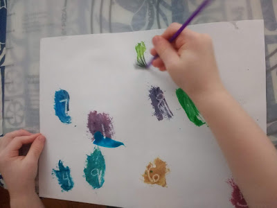 Toddler painting to reveal numbers in her secret message painting