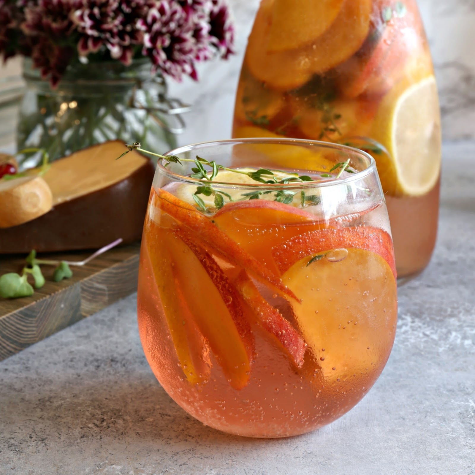 Sparkling gin and rose wine cocktail with peach and thyme.