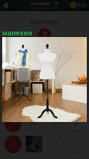 В комнате стоит манекен, на который одевают одежду во время изготовления