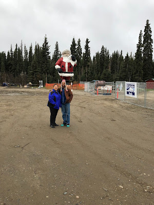 mom and I in front of a giant santa statue