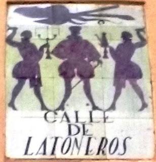 Antigua placa de la calle, de azulejos de cerámica. Con siluetas humanas en negro que portan objetos de latón.