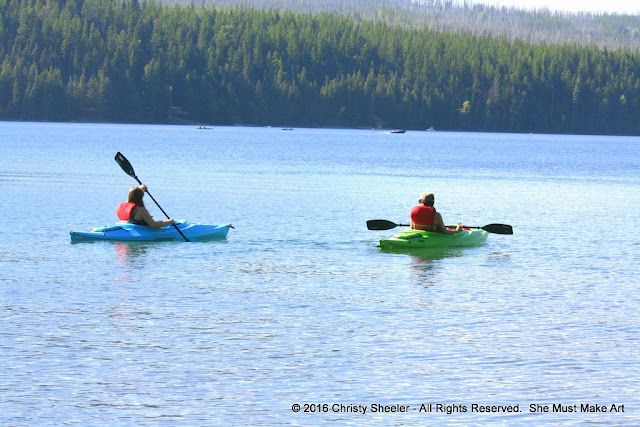 My daughter and I paddle out onto the lake in kayaks.
