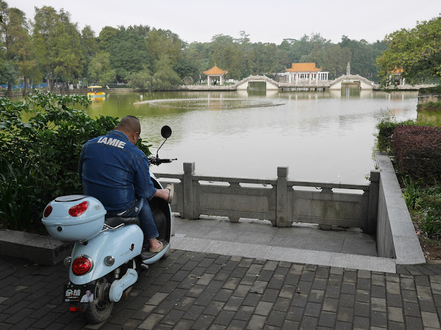 "man sitting on a motor scooter and wearing an ""IAMIE"" jacket"