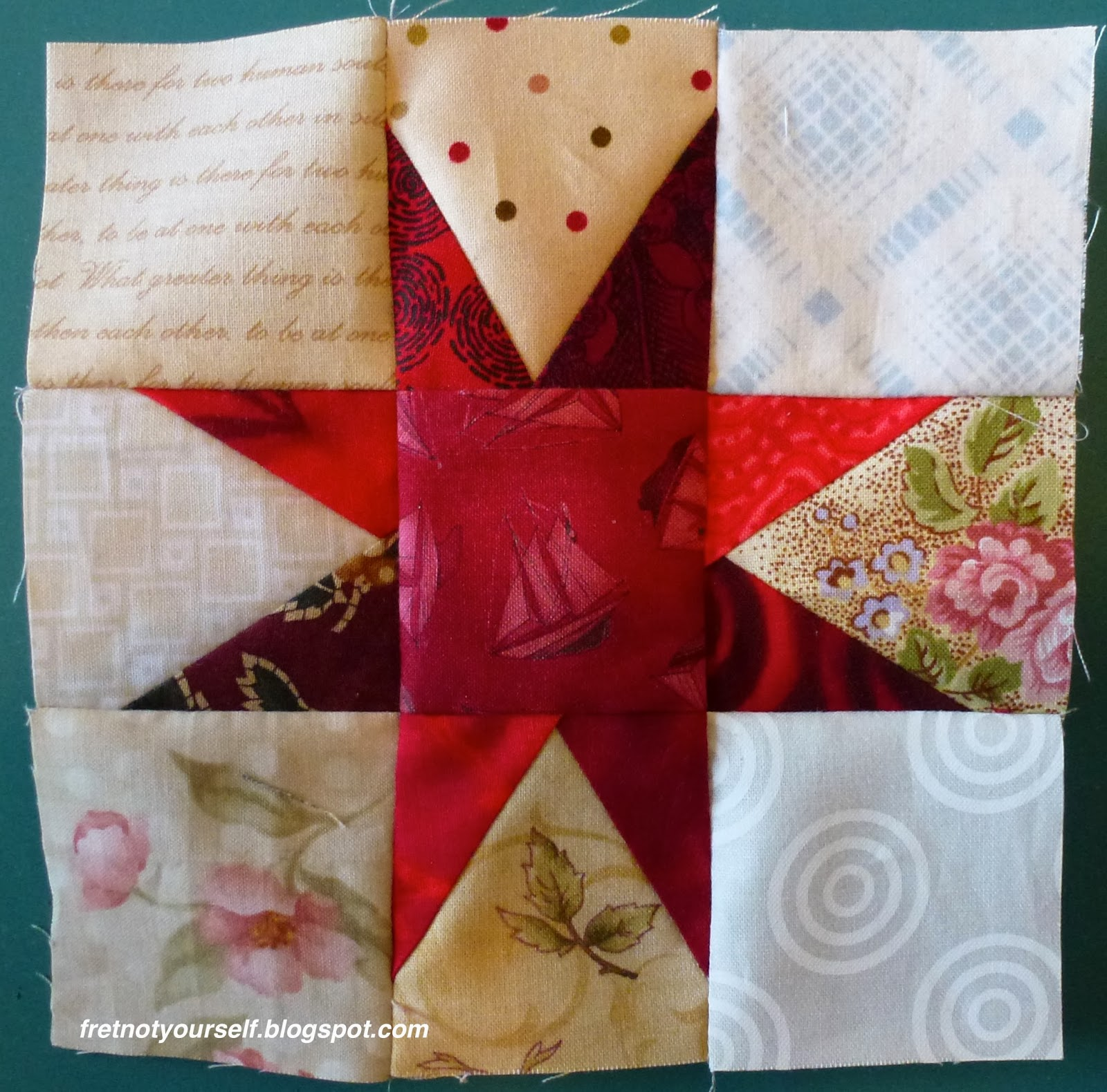 A variety of red fabrics create a star on the cream and white background of a Variable Star block.