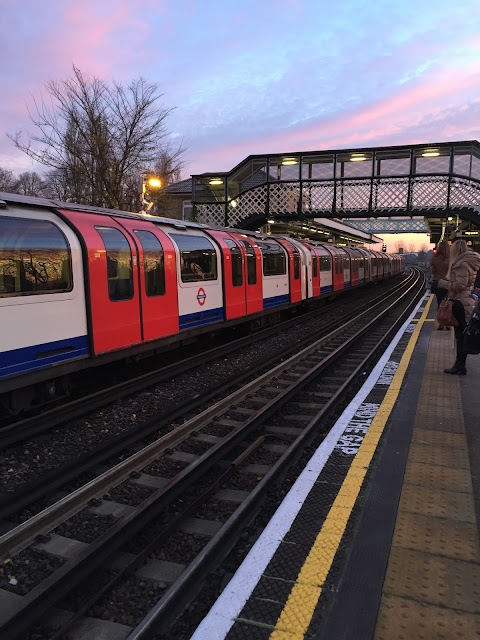 A tube station at sunrise with a train in the station and people waiting on the platform