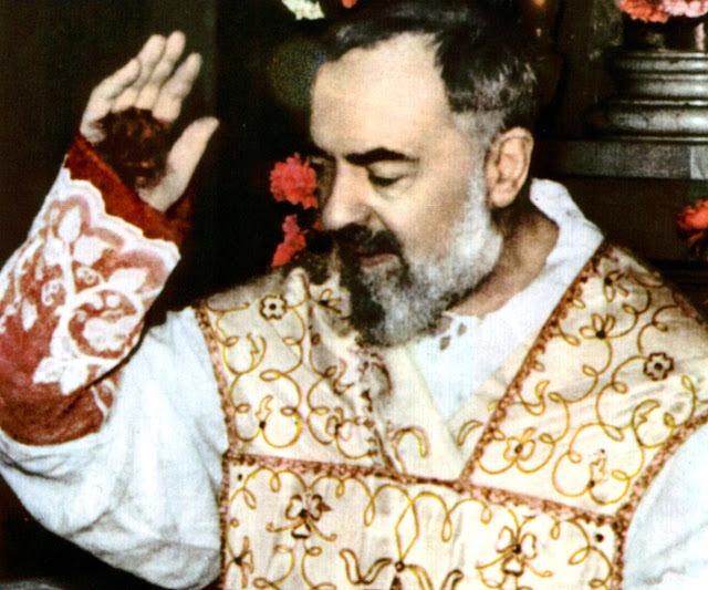 O santo Padre Pio abençoa na Missa. Podem-se apreciar os estigmas na mão.