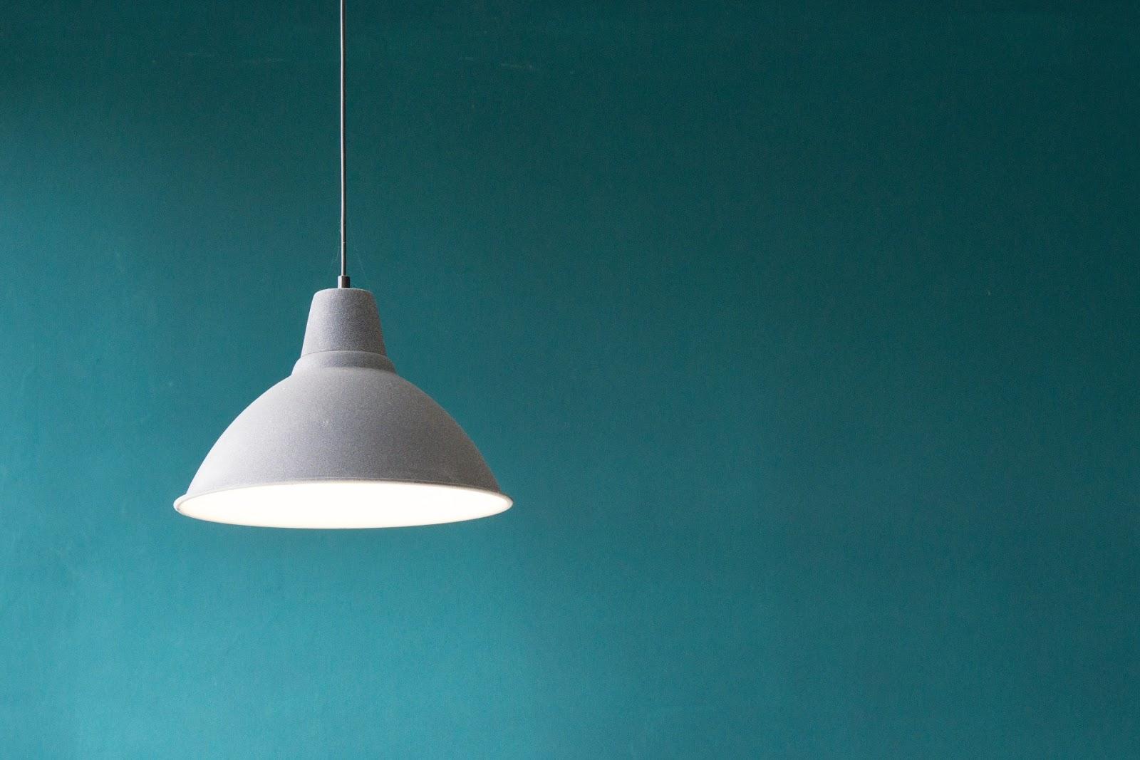 Biała okrągła lampa na tle zielonej ściany