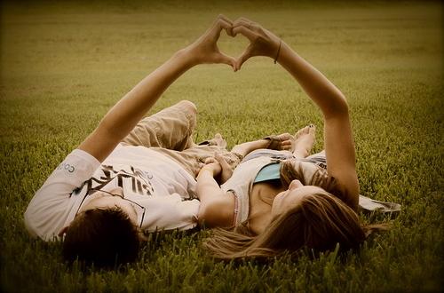 Pareja de chico y chica tumbados en el campo, haciendo un corazón con las manos.
