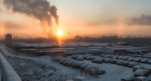 Промышленные районы с трубами, из которых идет огромное количество дыма. На улице мороз, видно солнечное гало.