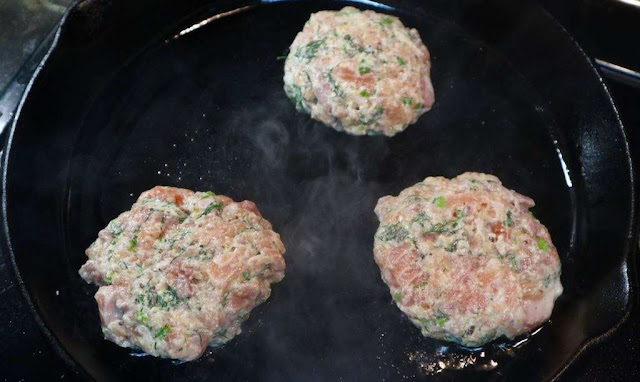 3 salmon burgers cooking away on the cast iron pan