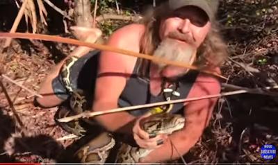 أمريكي يمسك بأفعى عملاقة بيديه العاريتين