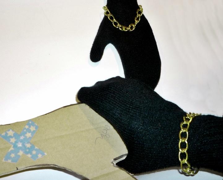 Zwei schwarze Fäustlinge, Goldkette und eine Pappschablone