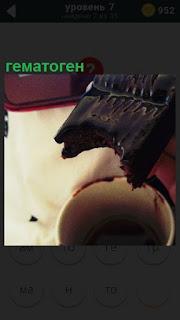 Показана сладость гематоген, от которой откушено и кружка рядом