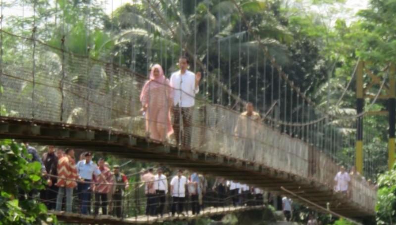 Presiden Jokowi bersama Iriana melintasi jembatan gantung di Lebak, Banten