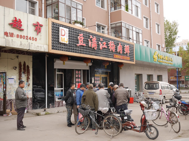 group of men watching and playing a game in front of a dog meat restaurant in Mudanjiang, China