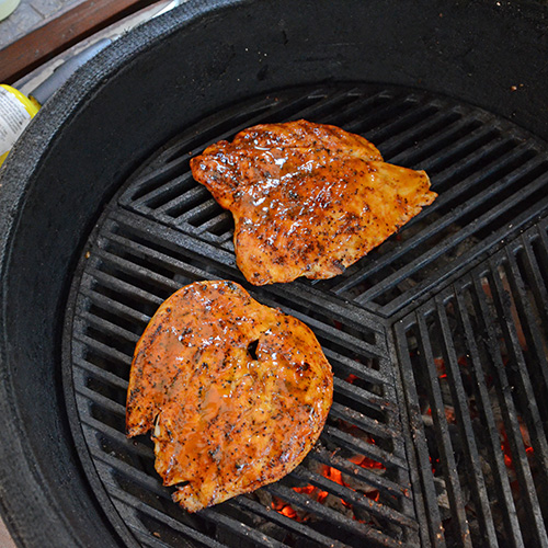 Grilling butterflied chicken breasts on a kamado grill on Craycort Cast Iron Grates