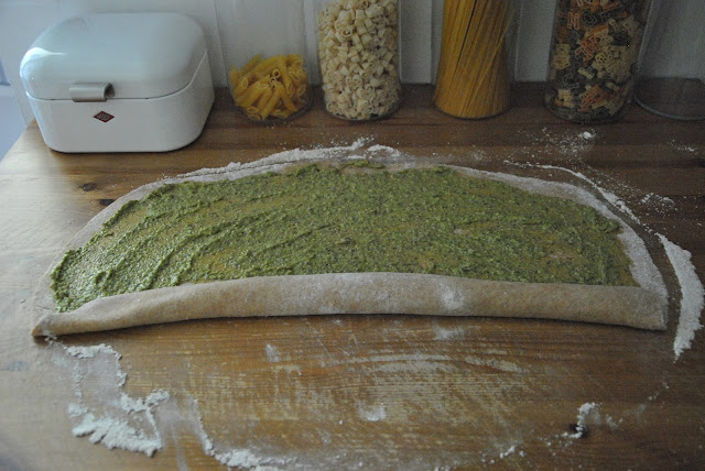 Brotteig rechteckig auswellen und mit Pesto bestreichen