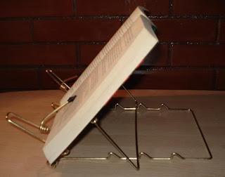Libro en posición correcta, abierto y colocado sobre un atril.