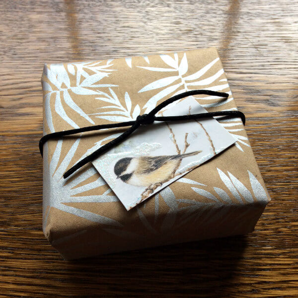 gift box wrapped with metallic silver screen printed kraft wrapping paper with foliage design, black silk cord tie and chickadee gift tag