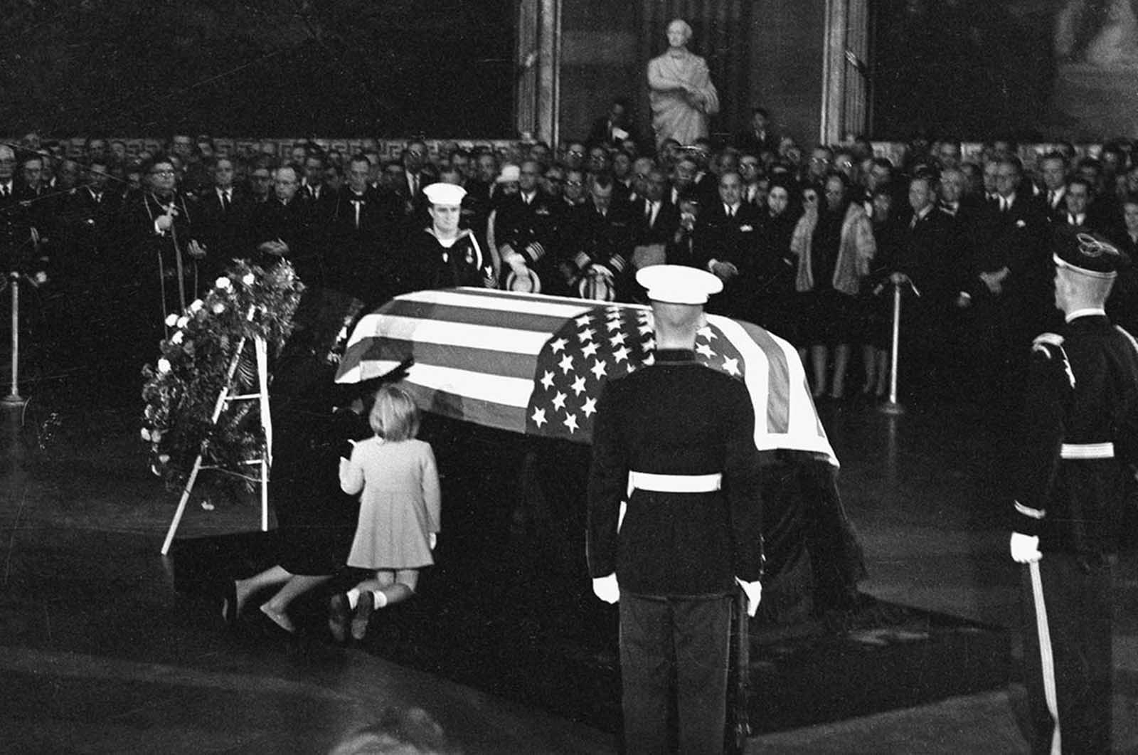 Widow Jacqueline Kennedy kneels and reaches out to touch the casket of her slain husband, John F. Kennedy, in the rotunda of the Capitol in Washington, District of Columbia, on November 24, 1963. Their daughter Caroline kneels beside her.