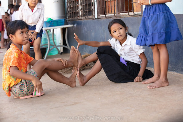 Two girls sit on the ground opposite each other with their feet touching making a hurdle for the other girls to jump over