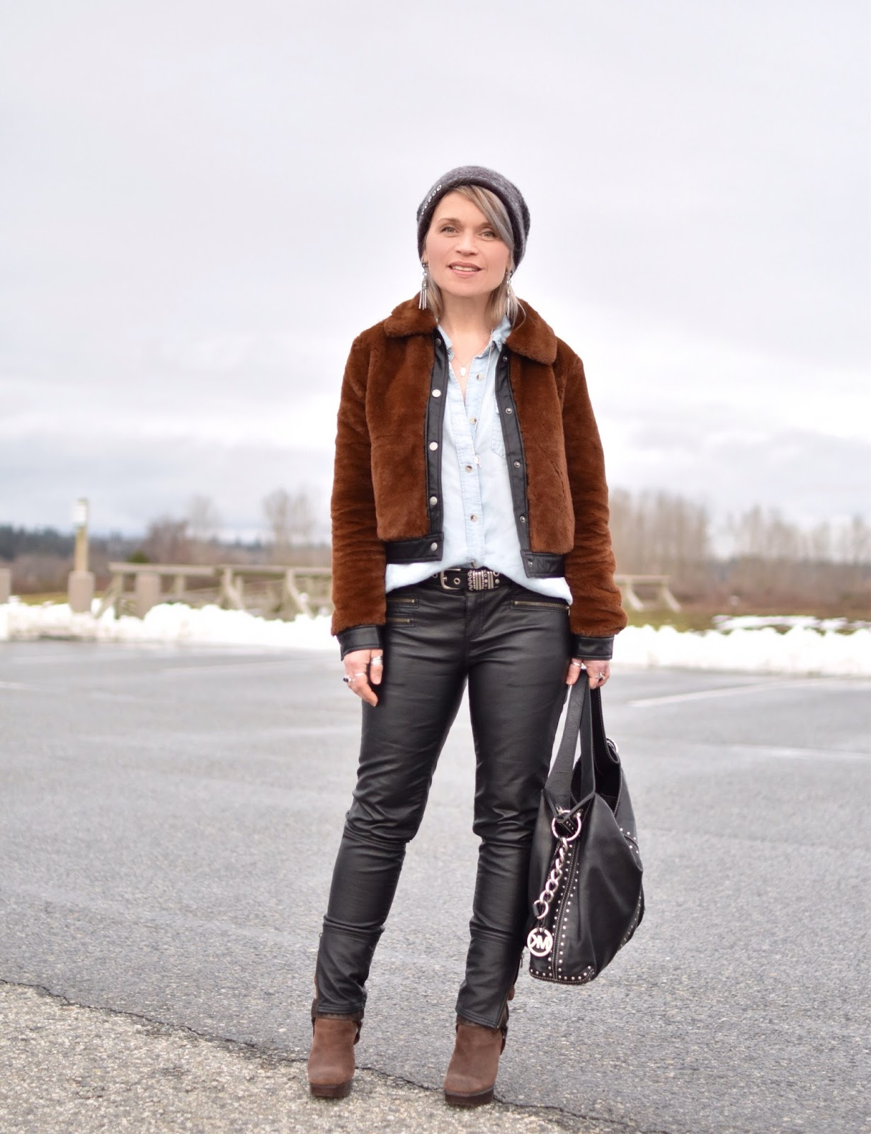 Monika Faulkner outfit inspiration - styling a chambray shirt and vegan leather jeans with a furry bomber, harness boots, and woolen beanie