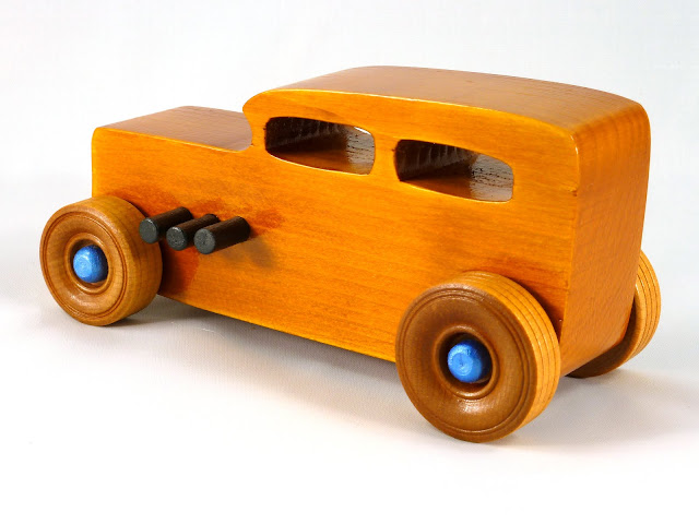 Left Rear - Wooden Toy Car - Hot Rod Freaky Ford - 32 Sedan - Pine - Amber Shellac - Black Pipes - Metallic Blue Hubs