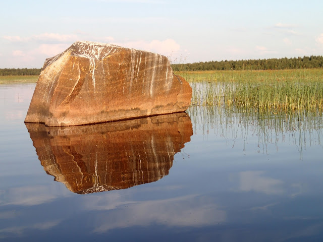 Komea lohkare pistää esiin tyynestä vedestä