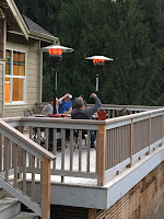 Photo of people sitting around table on an outside deck eating dinner at Sno-Valley Vegan Potluck. https://trimazing.com/