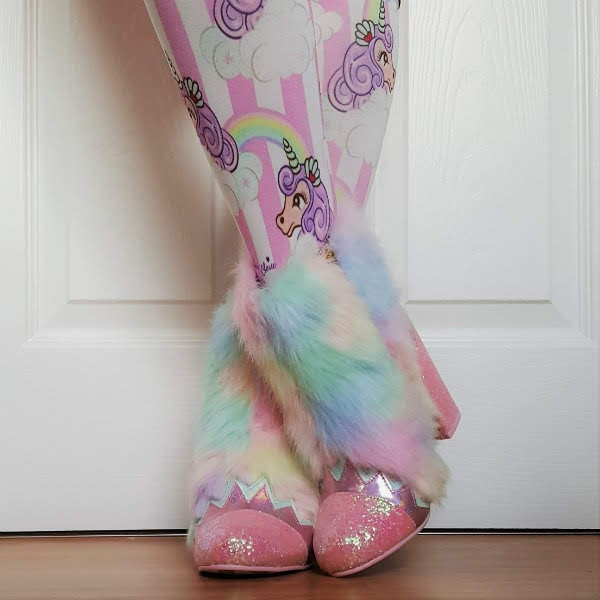 crossed legs wearing furry pastel rainbow ankle boots