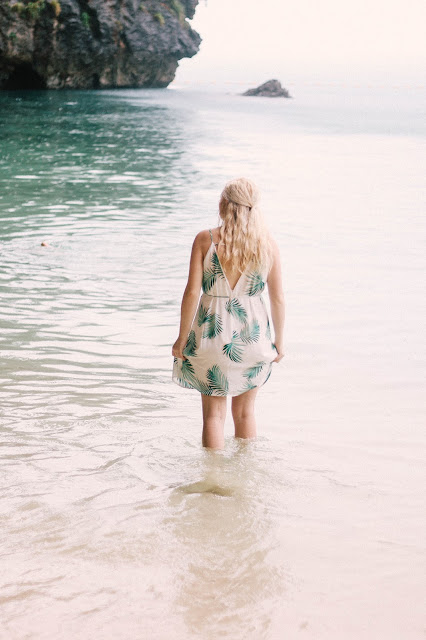 Fashion and Travel Blogger GlobalFashionGal (Brianna Degaston) wearing a palm tree leave printed dress in Railay Beach, Thailand.