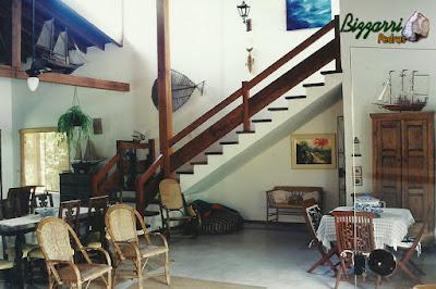Escada de concreto revestida de madeira com o corrimão de madeira para a parte superior e no piso o cimento queimado branco com detalhe em tijolo.