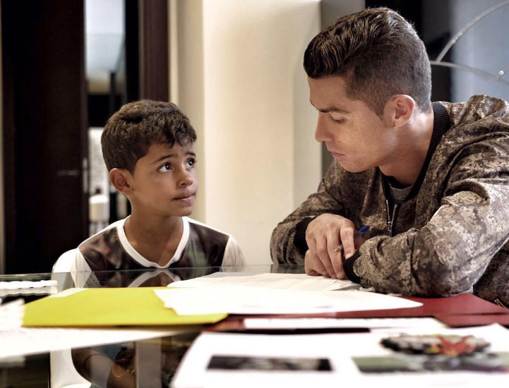 Aww! Ronaldo helps out his son with homework
