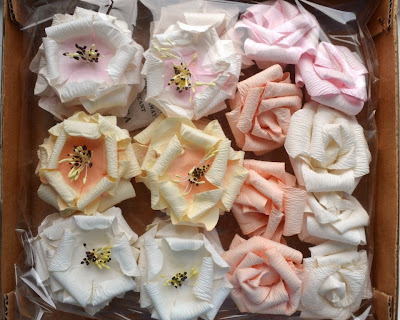 cardboard tray of paper flowers sealed in clear cellophane.  There are 6 large tea roses on the left in pale pink, apricot and white with yellos stamens. On the right are 10 miniature roses in pink (2), apricot (3) and creamy white (3).