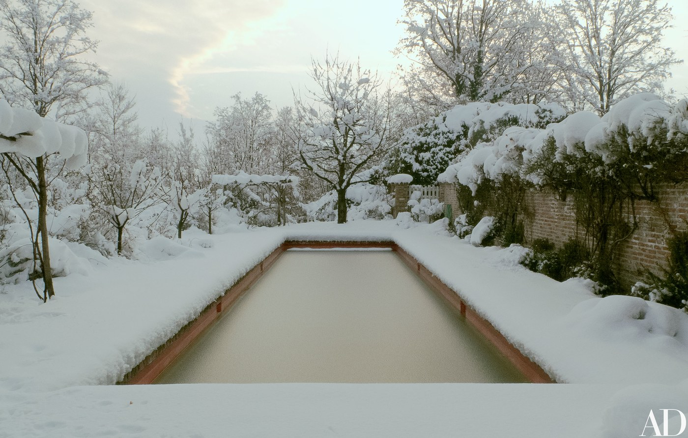 Snow covered natural pool on Oberto Gili's  farm in Italy