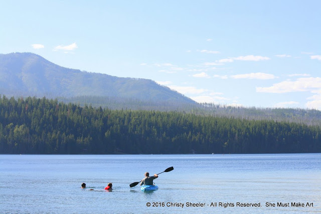 My husband out on the lake in the blue kayak.  My two children swim off to his left.