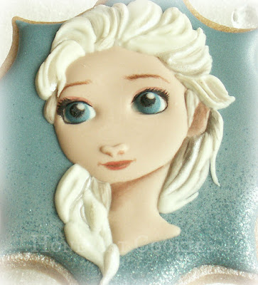 Finished handpainted decorated cookie of Elsa from Disney's Frozen, by Honeycat Cookies