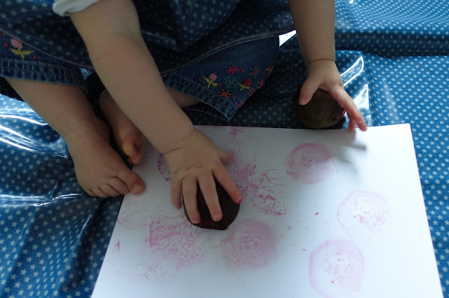 A baby making stamps with cut beetroot on a white piece of card on a wipe clean messy mat in blue with small white stars