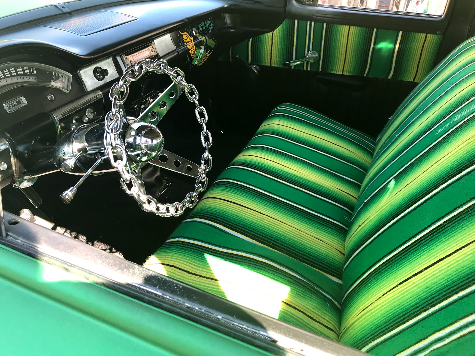 Image;Woman looking and showing the inside of a vintage car at the Dallas Car Show in Deep Ellum