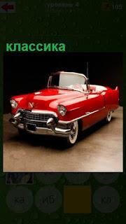 стоит красный открытый автомобиль классика