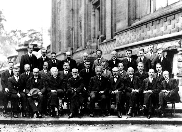 1927 Solvay International Conference: physicists meet to discuss the newly formulated quantum theory.  (back row L to R) A. Piccard, E. Henriot, P. Ehrenfest, E. Herzen, Th. de Donder, E. Schrödinger, J.E. Verschaffelt, W. Pauli, W. Heisenberg, R.H. Fowler, L. Brillouin;  P. Debye, M. Knudsen, W.L. Bragg, H.A. Kramers, P.A.M. Dirac, A.H. Compton, L. de Broglie, M. Born, N. Bohr;  (Front row) I. Langmuir, M. Planck, M. Skłodowska-Curie, H.A. Lorentz, A. Einstein, P. Langevin, Ch.-E. Guye, C.T.R. Wilson, O.W. Richardson. The only woman is Marie Curie (front, 3rd from left).
