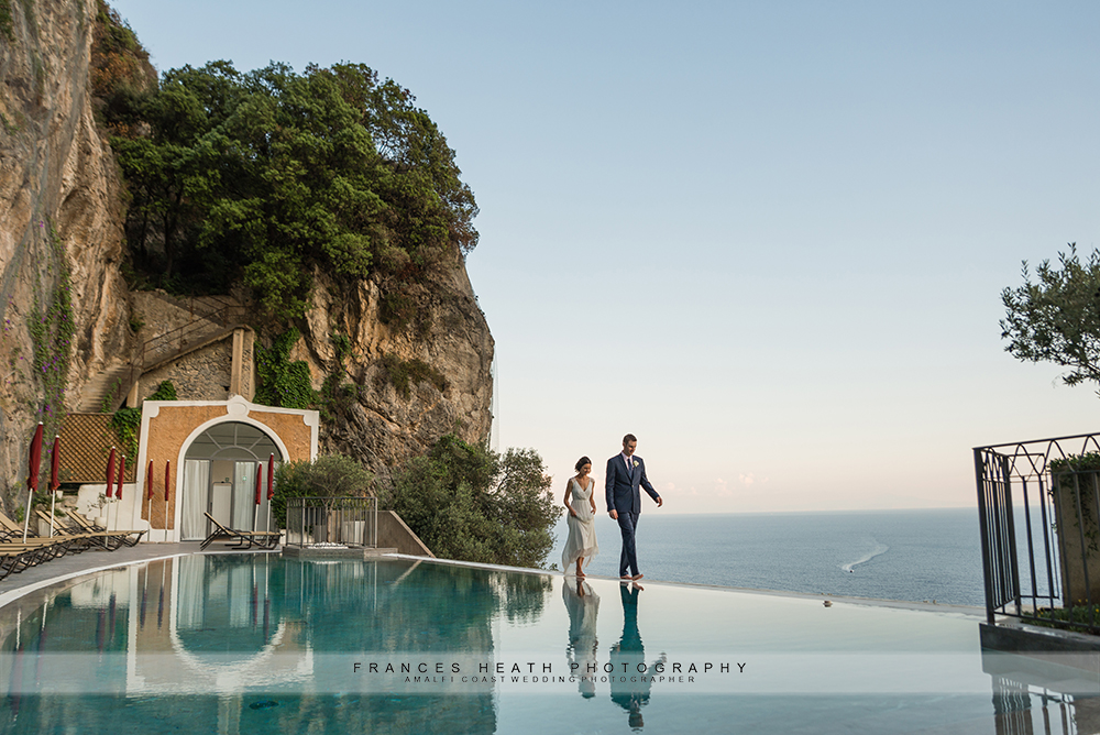 Bride and groom reflected in hotel Convento's pool