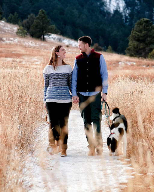 a young couple walks with their dogs along a snowy hiking trail in Boulder Colorado for their Engagement Session