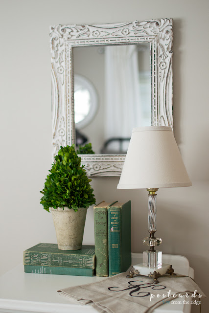 old green books with glass lamp and boxwood topiary
